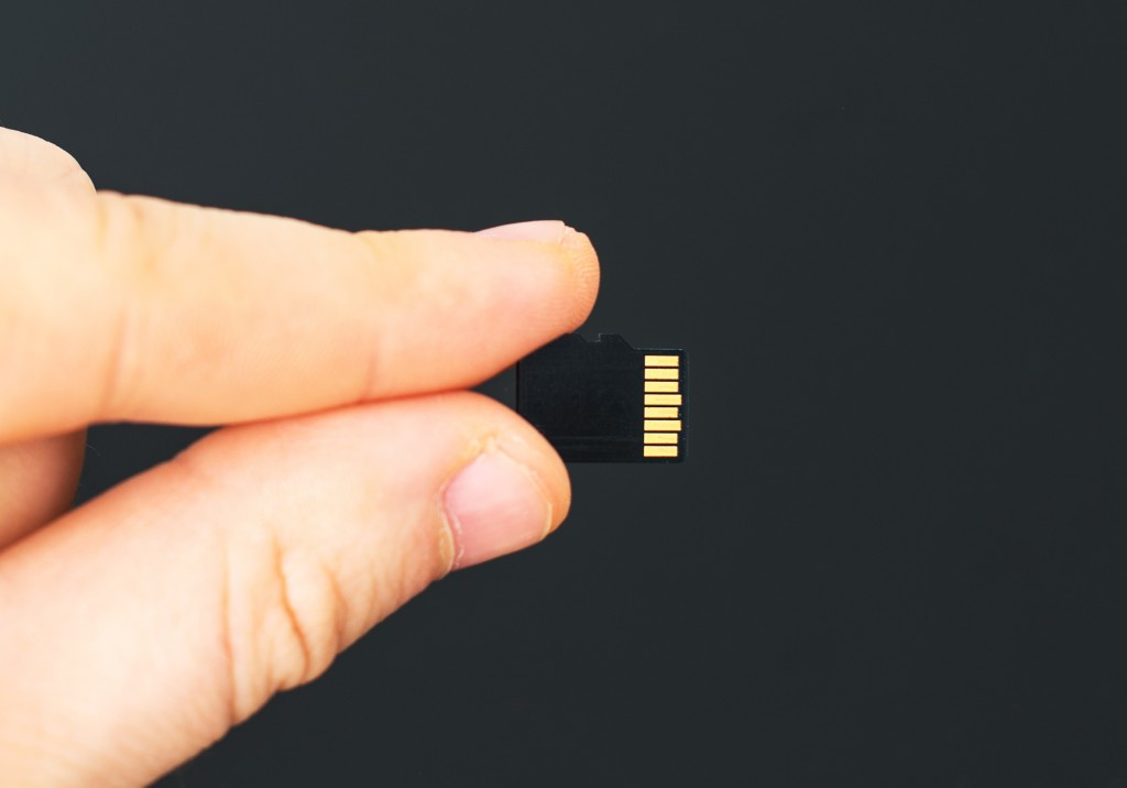 Male hand holding Micro SD card on black background.
